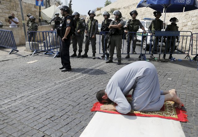 A Palestinian man prays as Israeli policemen guard during Friday prayers outside Jerusalem's Old City near the Arab East Jerusalem neighbourhood of Wadi al-Joz October 2, 2015. (Photo by Ammar Awad/Reuters)
