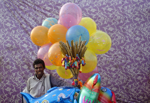 A vendor selling balloons waits for customers on the banks of the river Yamuna during the Hindu religious festival of Chatt Puja in New Delhi October 29, 2014. (Photo by Anindito Mukherjee/Reuters)