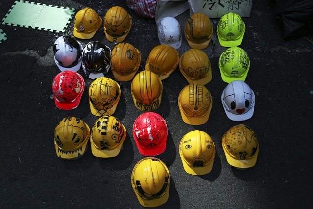 Decorated helmets, symbols of the pro-democracy movement, are left behind a barricade in the area occupied by protesters in Mongkok shopping district in Hong Kong October 30, 2014. A member of China's central bank's advisory body warned on Wednesday that Beijing will punish Hong Kong if pro-democracy protests that have paralyzed parts of the Chinese-controlled financial center for a month are allowed to continue. (Photo by Damir Sagolj/Reuters)