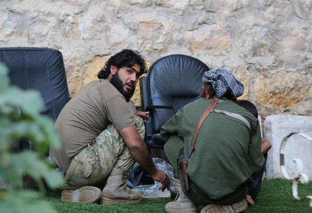 Rebel fighters of al-Jabha al-Shamiya (Levant Front) have their meal in the rebel-held al-Sheikh Said neighbourhood of Aleppo, Syria September 1, 2016. (Photo by Abdalrhman Ismail/Reuters)