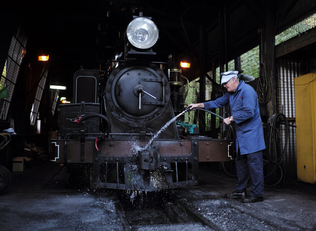 Puffing Billy steam engine fireman Barry Rogers, 70, washes locomotive 12A in the shed after hauling a train to Belgrave near Melbourne, October 20, 2014. (Photo by Jason Reed/Reuters)