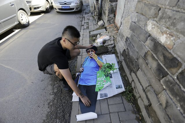 """Chinese artist ROBBBB prepares to paste his work in a traditional alleyway, or """"hutong"""", in central Beijing September 25, 2015. (Photo by Jason Lee/Reuters)"""