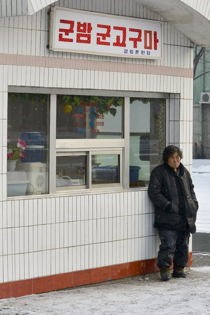 A resident of the capital stands outside a shop in February 2013, in Pyongyang, North Korea. (Photo by Andrew Macleod/Barcroft Media)