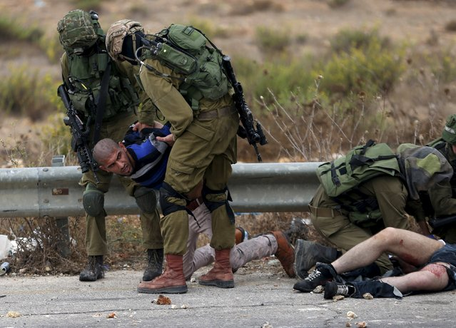 Israeli soldiers detain a Palestinian protester during clashes near the Jewish settlement of Bet El, near the West Bank city of Ramallah, October 7, 2015. (Photo by Mohamad Torokman/Reuters)