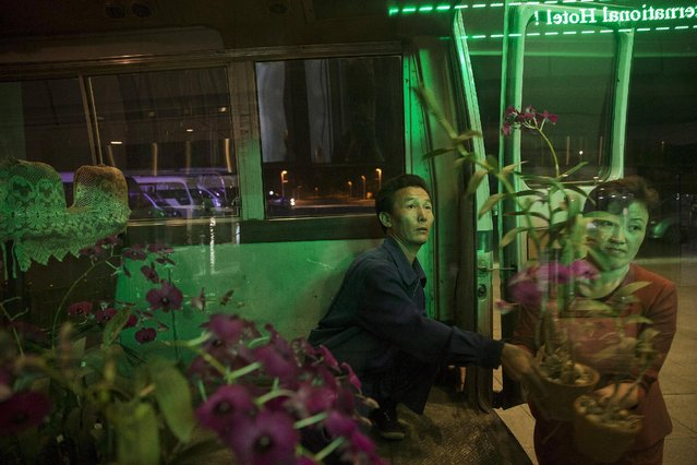 People carry flowers to decorate the lobby of a hotel in Pyongyang late October 7, 2015. (Photo by Damir Sagolj/Reuters)
