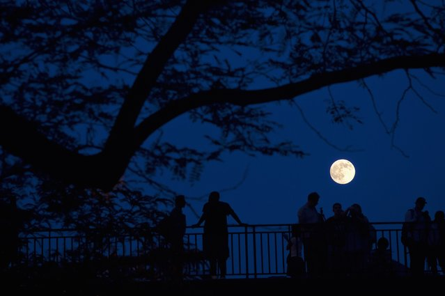 People stand and look at the Supermoon phenomenon from a bridge over 42nd St. in the Manhattan borough of New York July 11, 2014. Occurring when a full moon or new moon coincides with the closest approach the moon makes to the Earth, the Supermoon results in a larger-than-usual appearance of the lunar disk. (Photo by Carlo Allegri/Reuters)