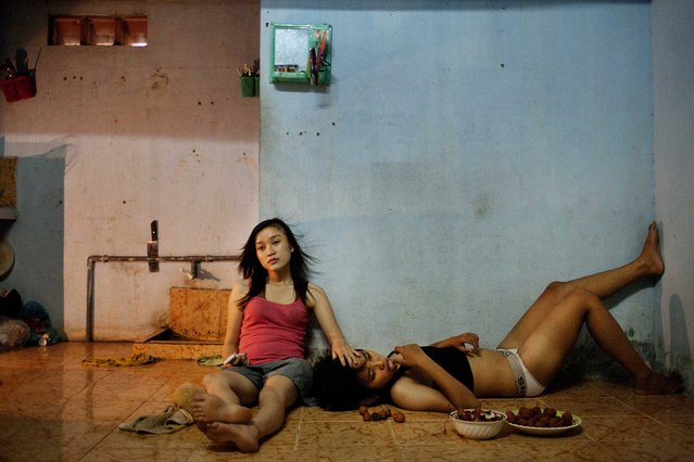 """This picture by Vietnamese photographer Maika Elan commissioned by Moss won the 1st prize stories for """"The Pink Choice"""" in the category """"Contemporary Issues"""" with in the 56th World Press Photo Contest, it was announced by the organizers on 15 February 2013 in Amsterdam, The Netherlands. Phan Thi Thuy Vy and Dang Thi Bich Bay, who have been together for one year, watch television to relax after studying at school. Vietnam has historically been unwelcoming to same-s*x relationships. But its Communist government is considering recognizing same-s*x marriage, a move that would make it the first Asian country to do so, despite past human rights issues and a long-standing stigma. In August 2012, the country's first public gay pride parade took place in Hanoi. This photograph is dated 22 June 2012 in Da Nang, Vietnam. (Photo by Maika Elan/EPA)"""