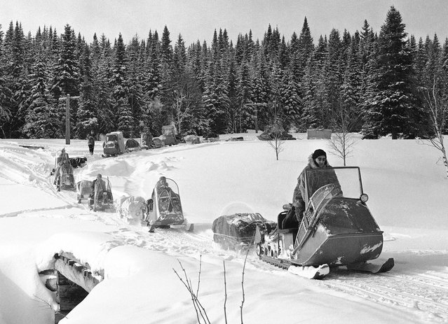Powered sledges break a trail through Maine's primitive Allagash Forest, on March 5, 1963. Twenty men, led by an expert on Arctic equipment, made an extended trip through the forest to test equipment. Robert Faylor, director of the Arctic Institute of North America, led the group. The sledges, called Polaris vehicles, are powered with engines about the size of an outboard motor and travel up to 8 or 10 miles an hour, depending on snow conditions. (Photo by Dan Grossi/AP Photo)