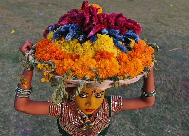 An Indian girl carrying Bathukammas, floral arrangements representing the giver of life, reacts to the camera during the Bathukamma festival dedicated to the Hindu Goddes Gauri in Hyderabad, India, October 20, 2015. (Photo by Mahesh Kumar A./AP Photo)