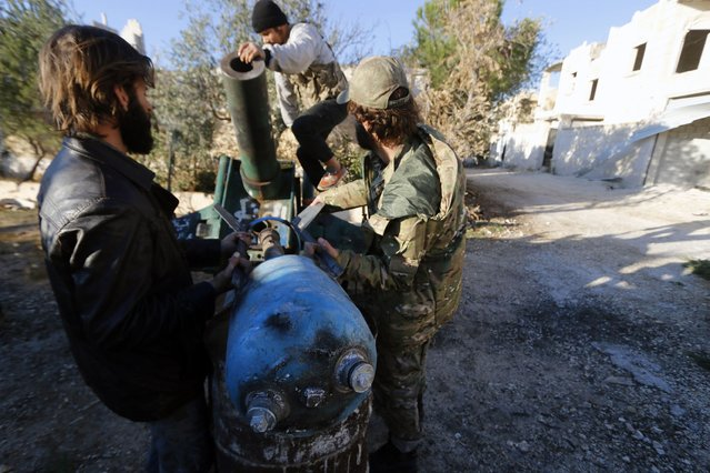 Fighters from the Noureddine Zanki movement, which operates under the Free Syrian Army, prepare an improvised explosive to fire towards forces loyal to Syria's President Bashar al-Assad at the frontline in Aleppo's al-Rashideen neighborhood November 27, 2014. (Photo by Hosam Katan/Reuters)