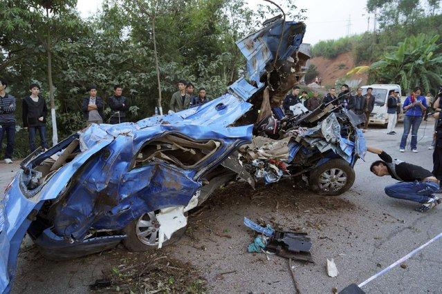 A man looks at the bottom of a destroyed minivan after it collided with a truck and fell off a ramp on the side of a street, in Nanning, Guangxi Zhuang Autonomous Region November 22, 2014. Eight people in the minivan, including a two-month-old baby and three young children, were killed in the accident on Saturday and a 14-year-old girl was injured and hospitalized, local media reported. (Photo by Reuters/Stringer)