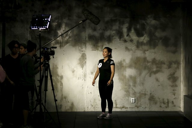 "A participant is interviewed before the start of a workout session during TV program ""The Body Show"" at a gym in Seoul, September 19, 2015. (Photo by Kim Hong-Ji/Reuters)"
