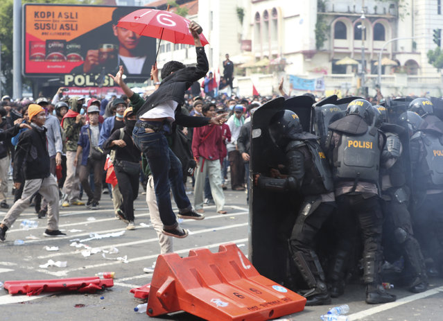 A protester tries to hurl a brick towards police trying block protesters from advancing towards the Presidential Palace during a rally in Jakarta, Indonesia, Thursday, October 8, 2020. (Photo by Achmad Ibrahim/AP Photo)