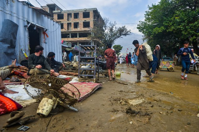 People go around a market area after a flash-flood in Charikar, Parwan province, on August 26, 2020. At least 46 people have been killed and hundreds of houses destroyed by flash floods as torrential rains lashed a city north of the Afghan capital, officials said on August 26. (Photo by Ahmad Sahel Arman/AFP Photo)