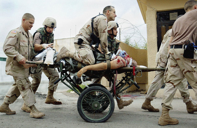 Combat Support Hospital Army Nurse supervisor Patrick McAndrew tries to save the life of an American soldier by giving him CPR upon arrival at the Combat Support Hospital in Baghdad, on April 4, 2005. (Photo by John Moore/AP Photo/The Atlantic)