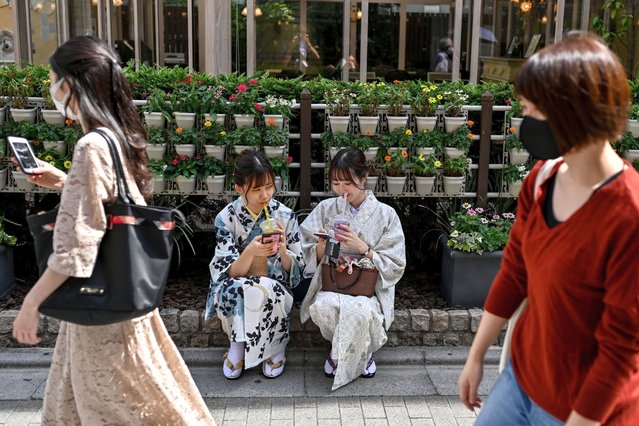 Women wearing traditional outfits take a break during a visit to Sensoji temple in Tokyo's Asakusa district on September 22, 2020. (Photo by Charly Triballeau/AFP Photo)