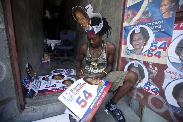 In this September 21, 2016 photo, a supporter of presidential candidate Maryse Narcisse, of the Fanmi Lavalas political party, cuts out campaign hats to distribute before a campaign rally in Port-au-Prince, Haiti. (Photo by Dieu Nalio Chery/AP Photo)