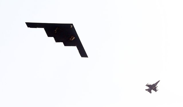 A U.S. air force B-2 Spirit stealth bomber (L) flies over Pyeongtaek, south of Seoul March 28, 2013. Yonhap reported that it was the first time for the bomber's drill to be confirmed on the Korean Peninsula and it said the bomber conducted a drill to strike a mock target, quoting a military source. (Photo by Sin Young-keun/Reuters/Yonhap)