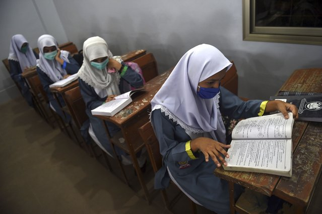 Students wearing facemasks attend a class at a school in Karachi on September 15, 2020 after the educational institutes were reopened nearly six months after the spread of the Covid-19 coronavirus. (Photo by  Rizwan Tabassum/AFP Photo)