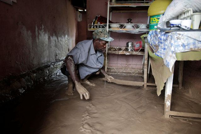 A man cleans out the water from his flooded house after Hurricane Matthew in Les Cayes, Haiti, October 5, 2016. (Photo by Andres Martinez Casares/Reuters)