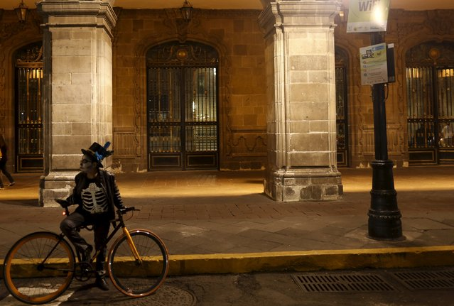"A man dressed up as a ""Catrin"", a Mexican character also known as ""The Elegant Death"", stands next to bicycle during the Catrinas parade in Mexico City October 31, 2015. (Photo by Carlos Jasso/Reuters)"