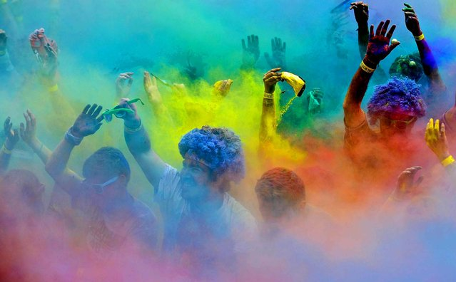 People celebrate in clouds of colored paint dust after The Color Run in Matosinhos, Portugal, on April 7, 2013. (Photo by Paulo Duarte/Associated Press)