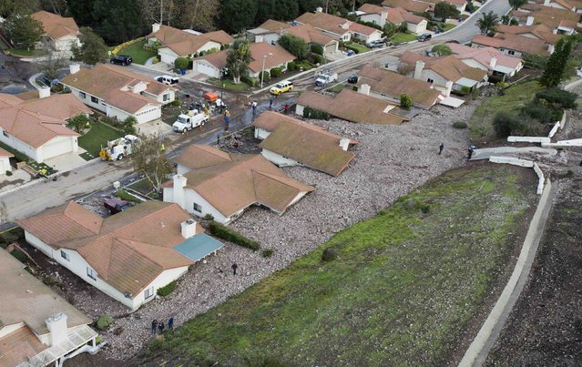 A group of houses are pictured after boulder-strewn rivers of mud swept down hillsides during a winter storm, in Camarillo Springs, California December 12, 2014. A Pacific storm pounded Southern California with heavy rain and high winds on Friday, triggering flash floods and mudslides that prompted the evacuation of hundreds of homes, damaged dozens of others and disrupted passenger rail service along the coast. One of the areas hardest hit on Friday was the community of Camarillo Springs, north of Los Angeles. (Photo by Mario Anzuoni/Reuters)