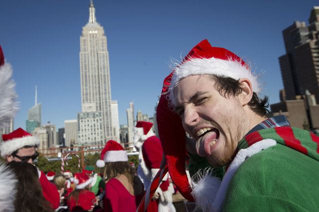 Revelers dressed in holiday theme costumes participate in SantaCon on a rooftop bar  Saturday, December 13, 2014, in New York. (Photo by John Minchillo/AP Photo)