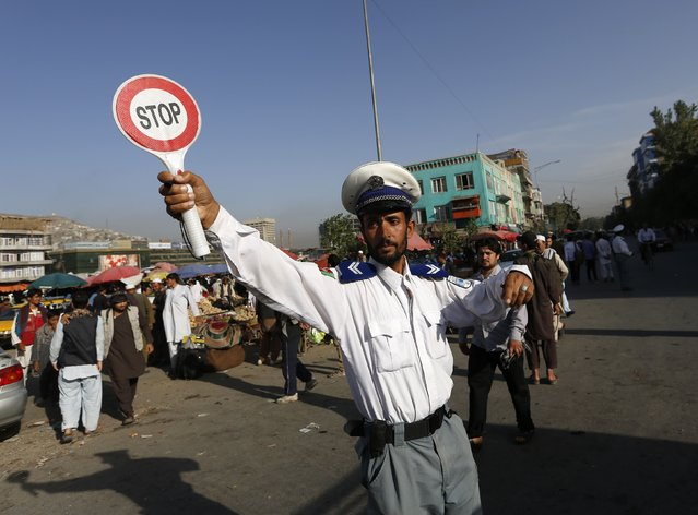 An Afghan traffic policeman directs vehicles on a busy road in Kabul August 31, 2014. (Photo by Mohammad Ismail/Reuters)