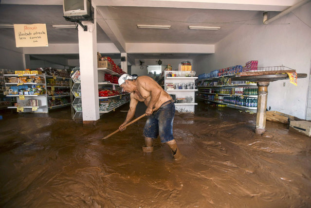 A man tries to clean the mud in a supermarket in Barra Longa, Minas Gerais, Brazil, 07 November 2015 after a retaining wall for an industrial waste dump collapsed on 05 November 2015. A breach in the levee unleashed a mudslide that flooded part of Bento Rodriguez, a village about 250 kilometres north of Rio de Janeiro, in which left eight people dead and another unknown number of people missing, and than 70 residents were injured. (Photo by Antonio Lacerda/EPA)