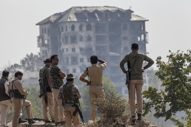 Indian policemen watch from distance at the government building where suspected militants have taken refuge during a gun battle in Pampore, on the outskirts of Srinagar, Indian controlled Kashmir, Wednesday, October 12, 2016. Handful of rebels holed up in a building in the Indian portion of Kashmir exchanged fire with government forces for the third straight day on Wednesday. (Photo by Dar Yasin/AP Photo)