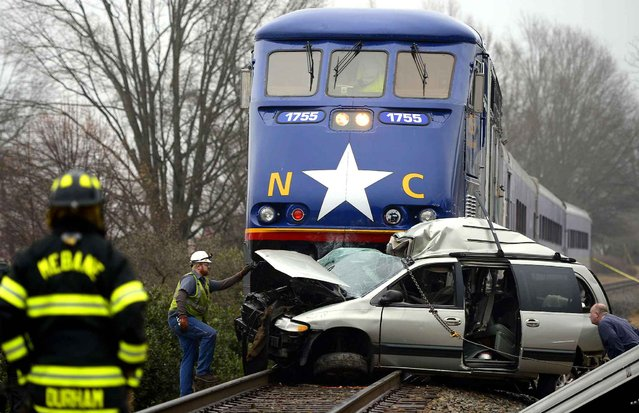 Officials investigate an accident between the 1755 Amtrak passenger train and a Dodge Caravan where the female driver of the van was killed in Mebane, N.C. on Tuesday, December 16, 2014. The collision occurred at the 4th Street crossing in downtown Mebane but the van was ultimately pushed almost half of a mile west. (Photo by Scott Muthersbaugh/AP Photo/Burlington Times-News)