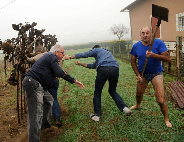 President of the Bird Protection league (LPO) Allain Bougrain-Dubourg (L) is evacuated by an inhabitant after clashing with the owner (R) of a plot where bird traps were found during an action against finch poaching, on November 9, 2015 in Audon, south western France. (Photo by Gaizka Iroz/AFP Photo)