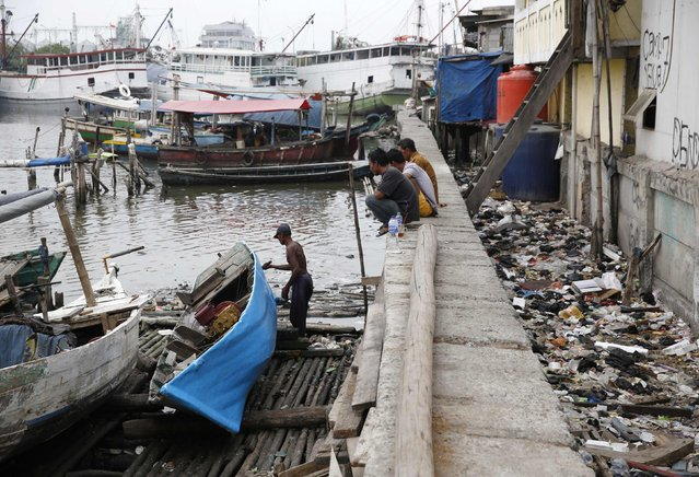 A man paints a boat on a makeshift dry dock next to the seawall protecting Luar Batang, one of the oldest kampongs in Jakarta, dating back to the16th century, in north Jakarta October 7, 2014. (Photo by Darren Whiteside/Reuters)
