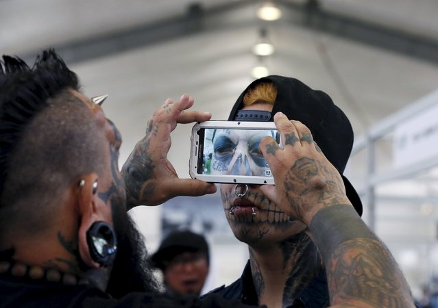 Venezuelan tattoo artist and body modifier Emilio Gonzalez (L) takes a picture of the eyeball tattoo on Eduardo Henriquez, 19, of Chile during the latin america convention of tattoo and suspension in Valparaiso city November 8, 2015. (Photo by Rodrigo Garrido/Reuters)