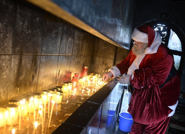 A man dressed as Santa Claus lights candles at a church in Bucharest, Romania on December 18, 2014. (Photo by Alex Nicodim/AFP Photo)