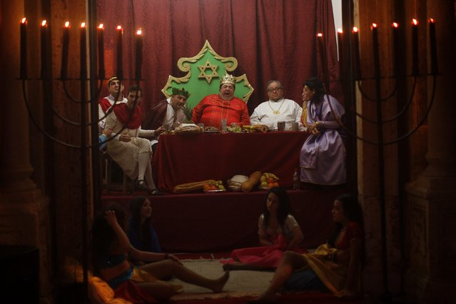 A man dressed as King Herod (C) yawns next to his harem as they take part in a re-enactment of the nativity scene, in Arcos de la Frontera, near Cadiz late December 20, 2014. (Photo by Jon Nazca/Reuters)