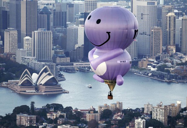 A hot air balloon from a fruit juice company, called Nudie, flies over Sydney Harbour, Monday, May 6, 2013. The roly-poly character of the Nudie company is drifting over Sydney as the company celebrates its 10th birthday. (Photo by Rick Rycroft/AP Photo)
