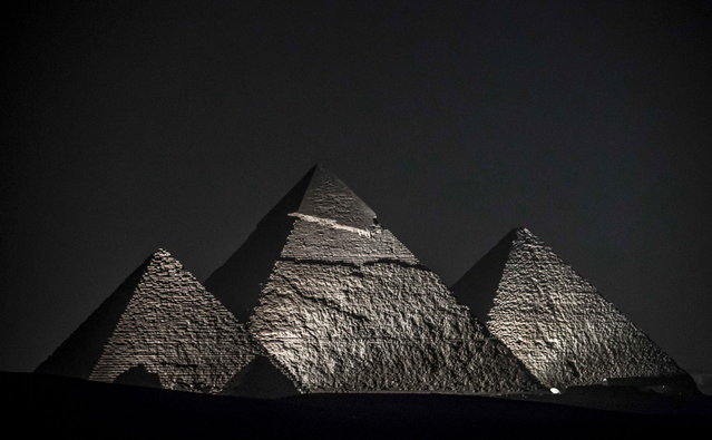 This picture taken on October 20, 2020 shows a general view of (R to L) the Great Pyramid of Khufu (Cheops), the Pyramid of Khafre (Chephren), and the Pyramid of Menkaure (Menkheres) at the Giza Pyramids necropolis on the southwestern outskirts of the Egyptian capital Cairo during an official ceremony launching the trial operations of the site's first environmentally-friendly electric bus and restaurant as part of a wider development plan at the necropolis. (Photo by Khaled Desouki/AFP Photo)