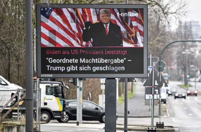 "A large news screen beside a street in Essen, Germany, showing US president Donald Trump, and a headline reading ""Biden as US president confirmed, orderly transfer of power – Trump declares defeat"" on Thursday, January 7, 2021. (Photo by Martin Meissner/AP Photo)"