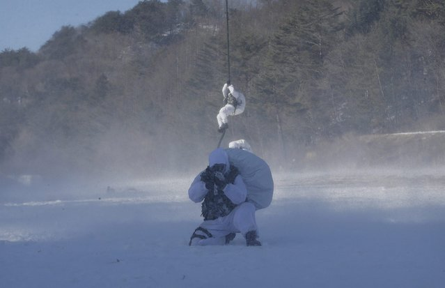 A South Korea's Amry Special Warfare Command (SWC) soldier takes his position while others rappel from a helicopter during a winter exercise in Pyeongchang, South Korea, Thursday, January 8, 2015. (Photo by Ahn Young-joon/AP Photo)