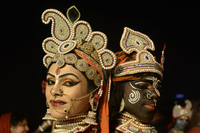 Indian dancers dressed as Hindu God Krishna and his consort Gopiyan are watched by devotees as they perform a dance or Raas Leela at The Chintpuri Temple in Jalandhar late November 25, 2015, on the occasion of Karthik Purnima or Full Moon Day. (Photo by Shammi Mehra/AFP Photo)