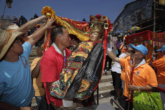 Villagers carry a statue of a Chinese god during a parade on the outlying Cheung Chau island in Hong Kong to celebrate the Bun Festival Tuesday, May 22, 2018. (Photo by Kin Cheung/AP Photo)