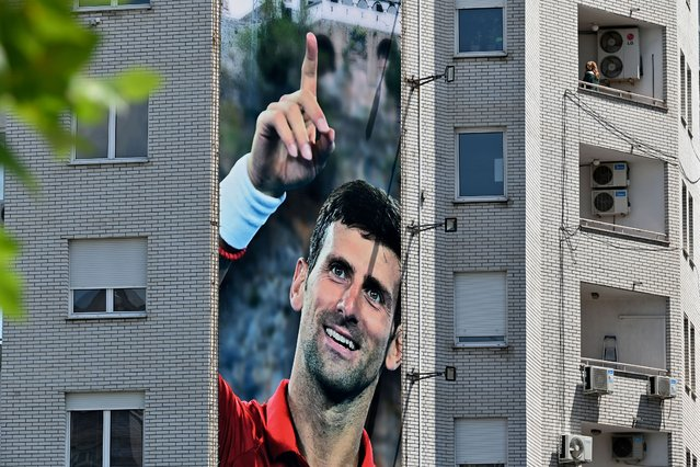 A billboard depicting Serbian tennis player Novak Djokovic and the Christian Orthodox monastery of Ostrog is seen on a building in Belgrade on June 24, 2020. Novak Djokovic has also tested positive for coronavirus on June 23, 2020 along with Grigor Dimitrov, Borna Coric and Viktor Troicki, after taking part in an exhibition tennis tournament in the Balkans featuring world number one Novak Djokovic, raising questions over the sport's planned return in August. (Photo by Andrej Isakovic/AFP Photo)