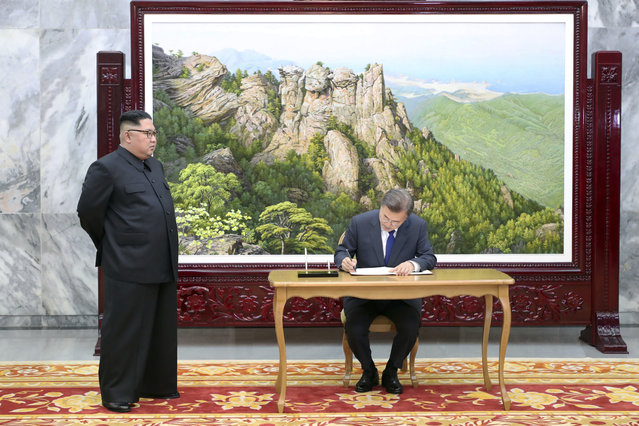 In this May 26, 2018 photo provided on May 27, 2018, by South Korea Presidential Blue House via Yonhap News Agency,  South Korean President Moon Jae-in writes on a visitor's book as North Korean leader Kim Jong Un, left, stands at the northern side of Panmunjom in North Korea. Kim and Moon met Saturday, May 26 for the second time in a month, exchanging a huge bear hug and broad smiles in a surprise summit at a border village to discuss Kim's potential meeting with U.S. President Donald Trump and ways to follow through on the peace initiatives of the rivals' earlier summit. (Photo by South Korea Presidential Blue House/Yonhap via AP Photo)