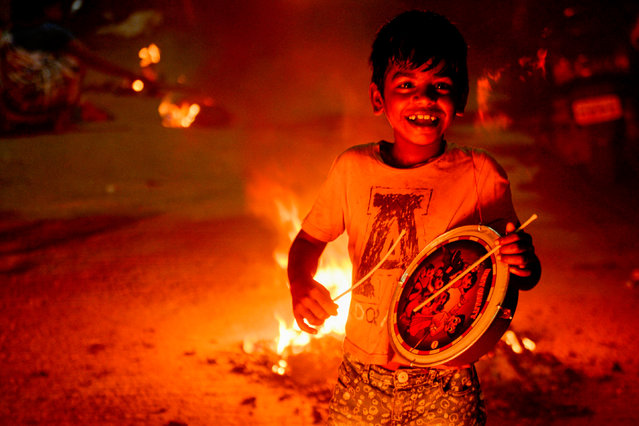 A boy plays the drum beside bonfires to celebrate Hindu harvest festival of Ponga in Chennai on January 13, 2021. (Photo by Arun Sankar/AFP Photo)