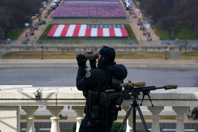A law enforcement personnel monitor from a balcony in Washington, DC, on January 20, 2021, during the inauguration of US President-elect Joe Biden and Vice President-elect Kamala Harris. (Photo by Susan Walsh/Pool via AFP Photo)