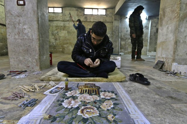 A man works on a mosaic artwork, copied from an original painting, in a workshop in Kafranbel town in the Idlib governorate January 17, 2015. (Photo by Khalil Ashawi/Reuters)