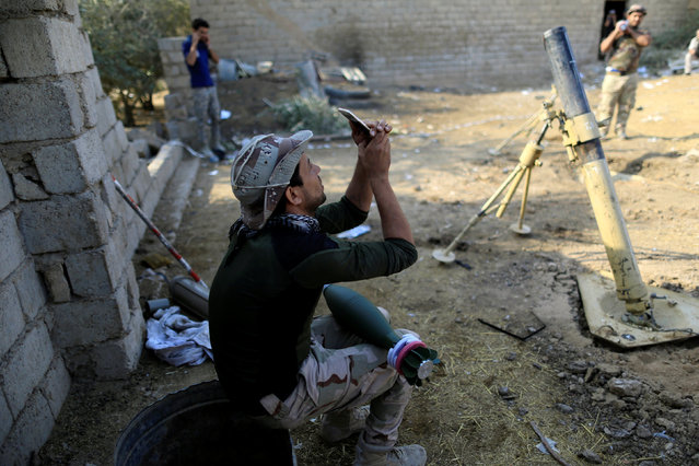 A soldier takes a selfie as rocket lies on his thigh during fighting with Islamic States militants, in the Shahrazad disrict of eastern Mosul, Iraq, November 6, 2016. (Photo by Zohra Bensemra/Reuters)