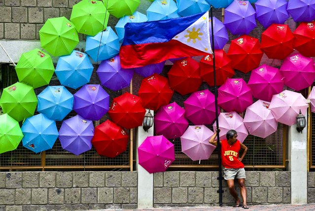 A man stands beside the Philippine flag as colorful umbrellas adorn a village hall in suburban San Juan, east of Manila, Philippines, on June 27, 2013. (Photo by Aaron Favila/Associated Press)